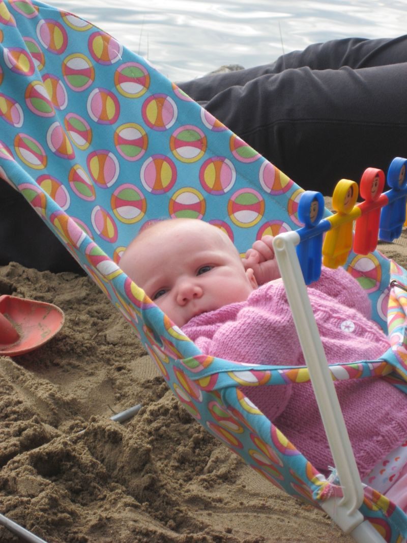 Ella relaxing on the beach, with her new sweater knit by her Grandma